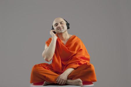 'eyes shut: Monk listening to music Stock Photo