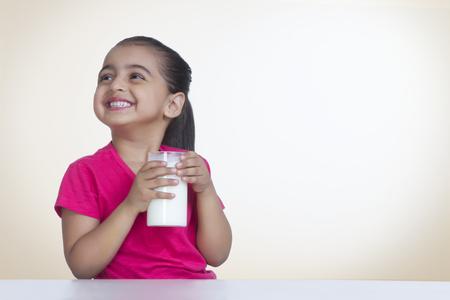 色付きの背景に対して牛乳のガラスと幸せな女の子