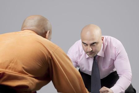 intimidating: Bald businessmen competing