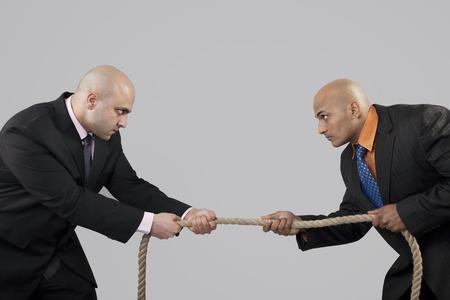 intimidating: Tug of war between two businessmen