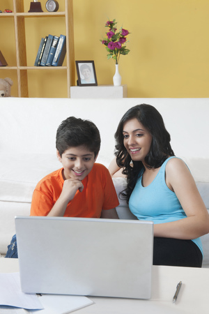 sleeveless top: Sister and brother watching laptop