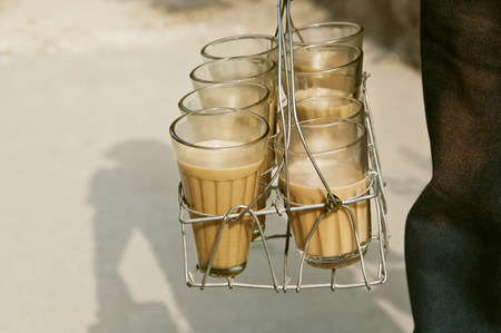 Glasses of chai in metal grid tray