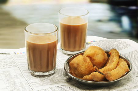 Close-up of morning chai with bhajiyas and fried potato balls on newspaper