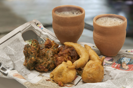 Indian pakoras,bhajiyas and fried potato balls with chai in traditional cup made of mud on a newspaper Stock Photo