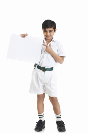 Full length portrait of boy in school uniform showing blank placard against white background Stock Photo