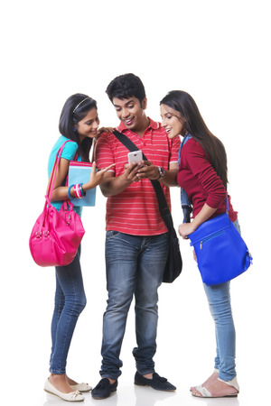 Full length of happy college students using mobile phone against white background Stock Photo