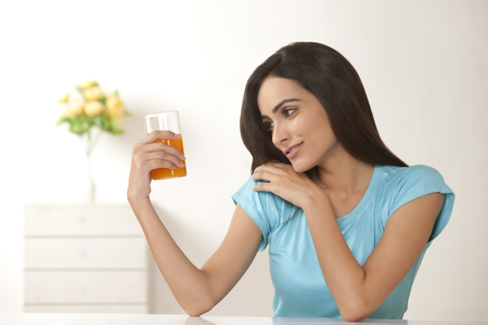 front house: Beautiful young woman looking at glass of orange juice at home