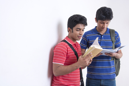Male university students reading books against wall