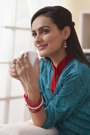 Beautiful Indian woman having coffee in living room Stock Photo