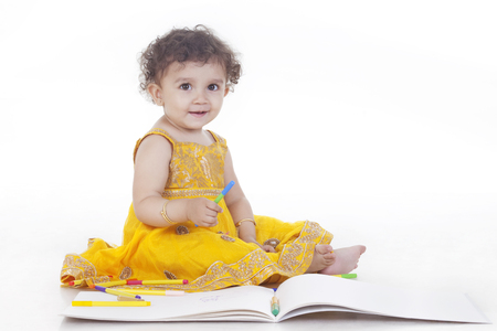 kameez: Full length of cute girl wearing traditional clothing coloring against white background