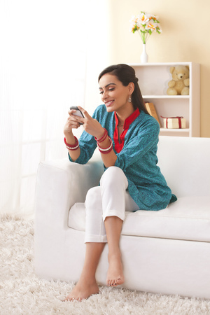 Full length of young Indian woman text messaging in living room