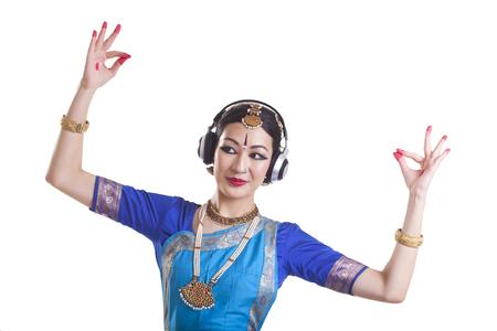 Woman wearing headphone while performing Bharatanatyam over white background
