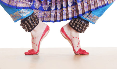 Traditional dancers feet performing Bharatanatyam over white background
