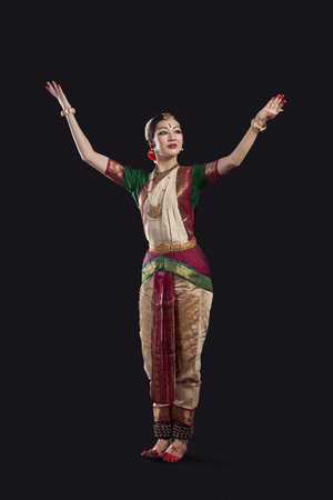 Full length of dancer with arms raised performing Bharatanatyam against black background