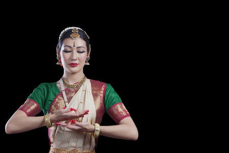 Bharatanatyam dancer with eyes closed performing over black background