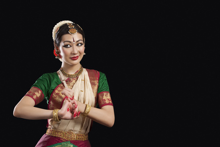 Young woman performing Bharatanatyam over black background Stock Photo
