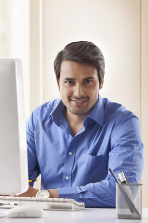 Portrait of handsome young businessman at computer desk in office