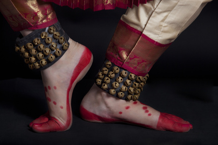 low section: Traditional dancers feet performing Bharatanatyam against black background