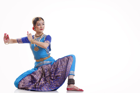 Full length of woman performing Bharatanatyam against white background