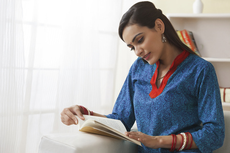 Young Indian woman reading book on sofa