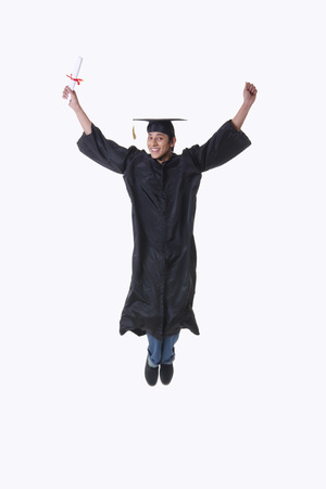 Full length portrait of excited graduate student in mid-air over white background