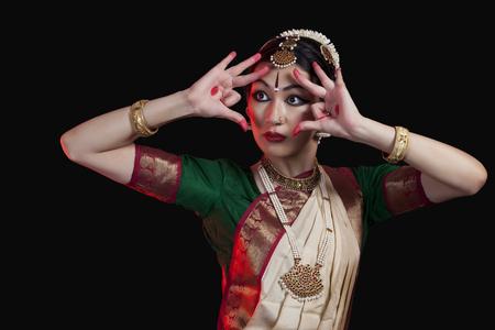 Furious Bharatanatyam dancer performing against black background