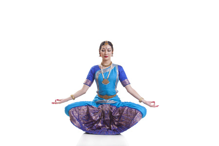 Dancer with eyes closed performing Bharatanatyam against white background
