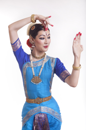 Beautiful woman in Bharatanatyam pose over white background
