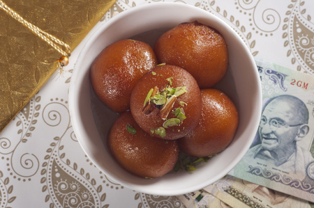 Top view of gulab jamun and currency