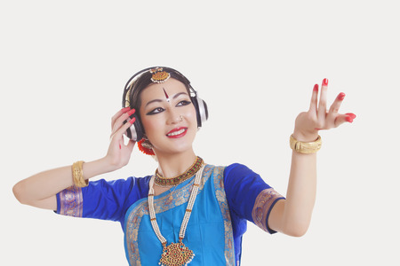 Bharatanatyam dancer wearing headphones while dancing over white background