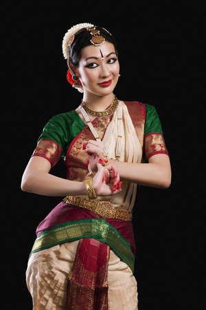 Beautiful woman performing Bharatanatyam on black background