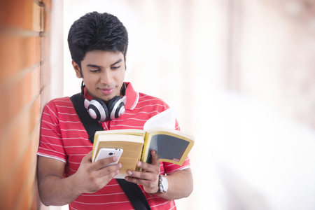 Young male student reading book in university