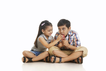 Full length girl feeding apple to brother while sitting over white background