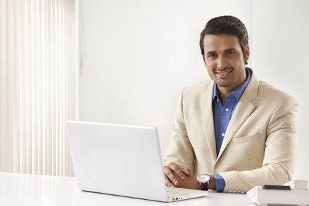 Portrait of young Indian businessman with laptop sitting at office desk