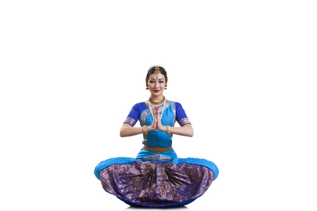 Portrait of dancer greeting while performing Bharatanatyam against white background