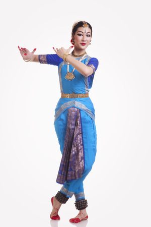 Full length portrait of beautiful woman performing Bharatanatyam on white background