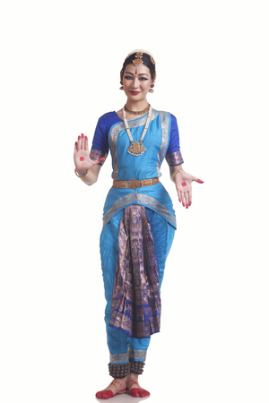 Full length portrait of woman in Bharatanatyam posture over white background Stock Photo