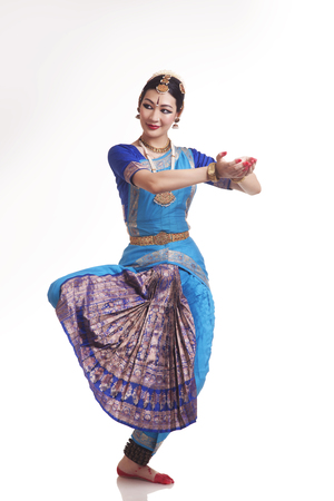 Full length of happy young woman performing Bharatanatyam over white background
