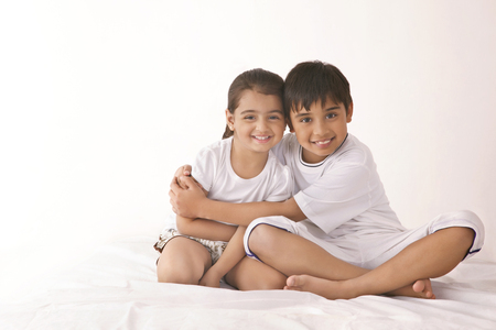 Portrait of happy brother embracing sister in bed Stock Photo