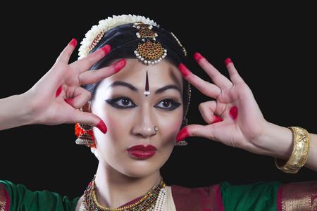 Close-up of young woman making Bharatanatyam gesture called Shakatam on black background Stock Photo