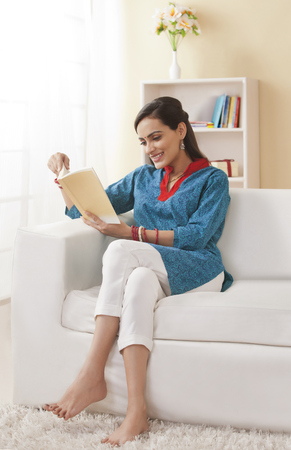 Full length of young Indian woman reading book on sofa