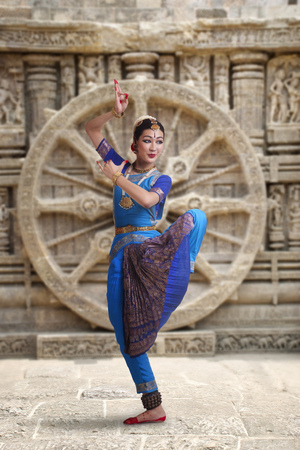 Full length of Bharatanatyam dancer performing against carved wall