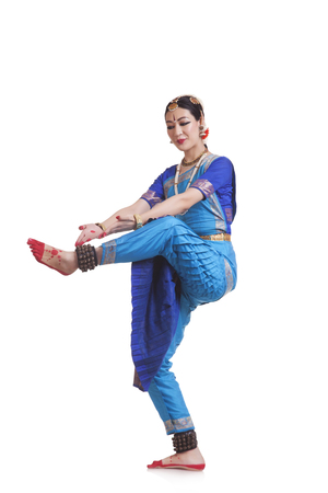 Full length of woman performing Bharatanatyam against white background