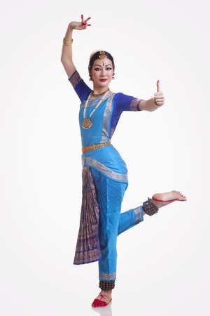 Full length portrait of confident young woman performing Bharatanatyam over white background