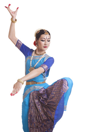 Dancer posing while performing Bharatanatyam against white background
