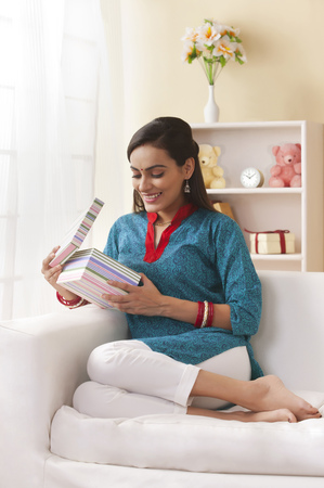 kameez: Full length of young married Indian woman opening gift box in living room