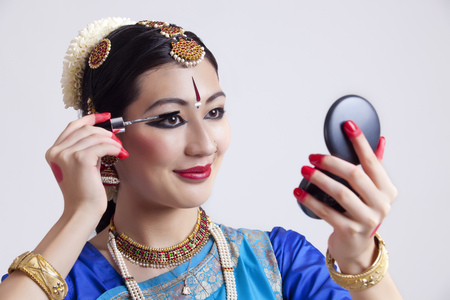 Beautiful Bharatanatyam dancer applying mascara over gray background