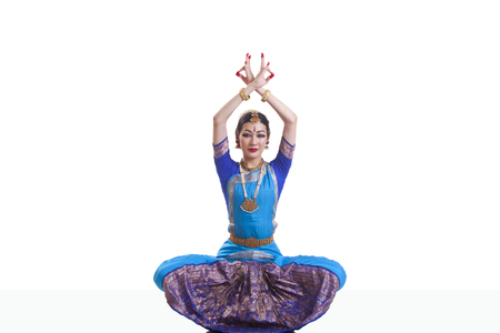 Portrait of dancer with arms raised performing Bharatanatyam isolated over white background