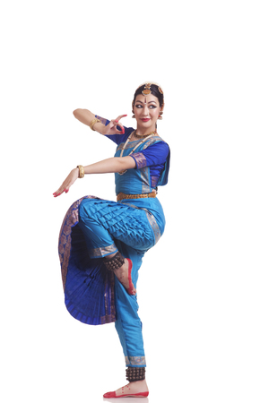 Full length of beautiful Bharatanatyam dancer performing on white background