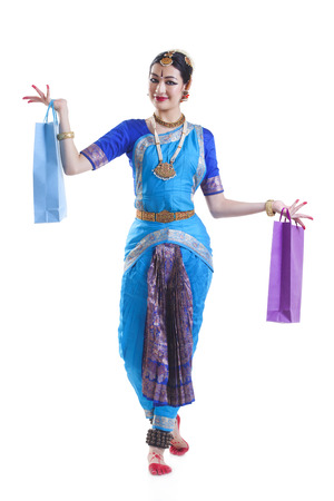 Full length of Bharatanatyam dancer with shopping bags posing over white background Stock Photo